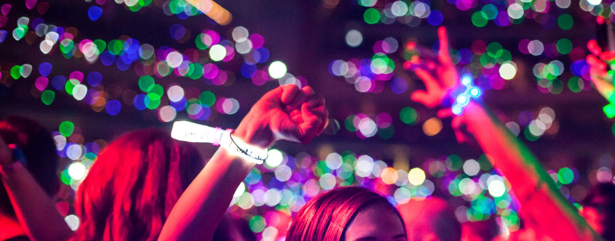 fans in the crowd of a concert with led bracelits