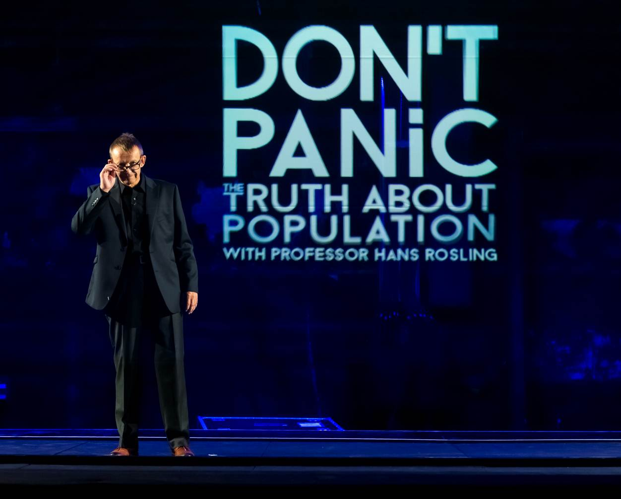 Hans Rosling standing on the stage, presenting Dont Panic - The Truth About Population Sizes